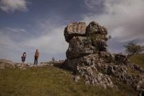 Deux personnes au lin, dans un paysage de causse avec un rocher au premier plan