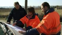 Une femme et deux hommes en tenue de travail étudient une carte sur le capot d'une voiture
