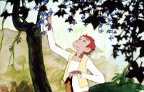 Un jeune singe cueille une fleur bleue dans un arbre