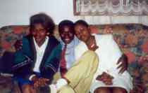 Photo de famille d'un homme et de ses deux femmes, sur un canapé