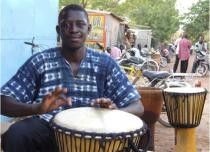 Jules César, artisan fabriquant de djembé, joue du djembé