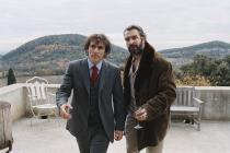 Albert Dupontel et Jean Dujardin marchant d'un air décidé sur une terrasse