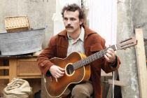 Comédien dans le rôle de Georges Brassens jouant de la guitare
