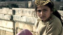 Jeune roumaine coiffée d'une couronne, adossée à un mur de pierre