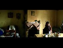 Une femme est assise, seule, dans une salle à manger aux murs usés