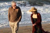 Un homme et une femme marchent au bord de l'eau, à la plage