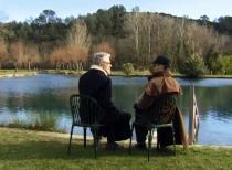 Deux personnes, de dos, sont assisent face à un lac