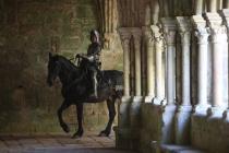 Un chevalier à cheval avance entre les arches du patio d'une abbaye