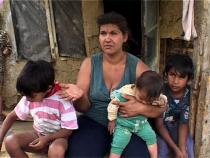 Une mère rom, entourée de ses trois enfants, fait la manche