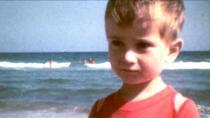 Petit garçon portant un t-shirt rouge, devant la mer