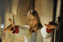 Une petite fille blonde, dans un couloir, tend les bras vers la caméra
