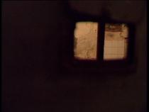 Par un fenestrou grillagé, on apperçoit l'intérieur d'une cellule de prison